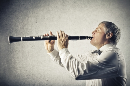 jazz time: musician plays clarinet on gray background