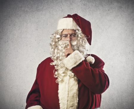 funny Santa Claus makes a sign to be silent