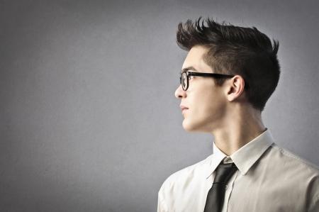 hombre de perfil: joven hombre de negocios en el perfil sobre un fondo gris