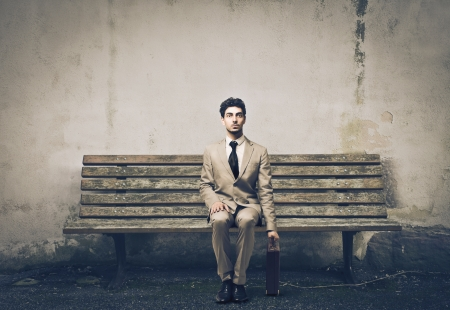 elegant man sitting on a bench waiting for undecided photo