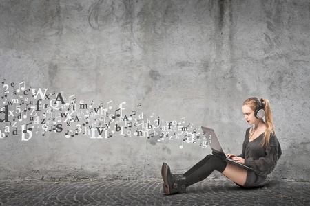 poezie: tiener zittend op de vloer met laptop en koptelefoon voor muziek