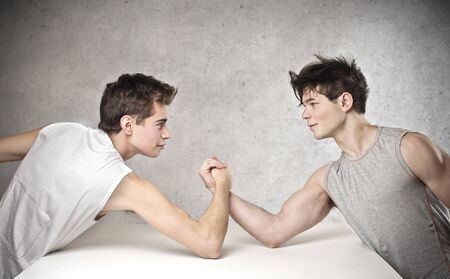 young boys playing arm wrestling photo