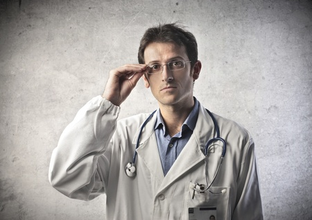 serious doctor: doctor with a white coat on gray background