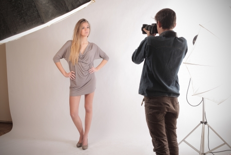 photo shooting: blond model posing in front of photographer
