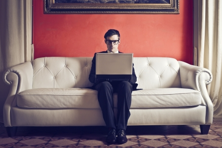 businessman sitting on sofa with laptop photo