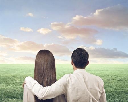 hugging couple: loving couple looking landscape