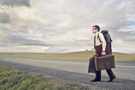 hard way: businessman with many suitcases walking on deserted road