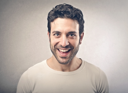 Surprise: portrait of handsome man smiling on gray background