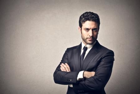 lideres: hombre de negocios con los brazos cruzados sobre un fondo gris