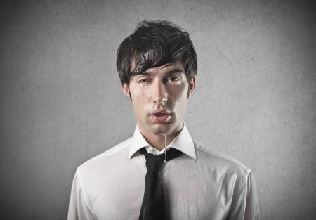 wet men: portrait of sad man wet on gray background