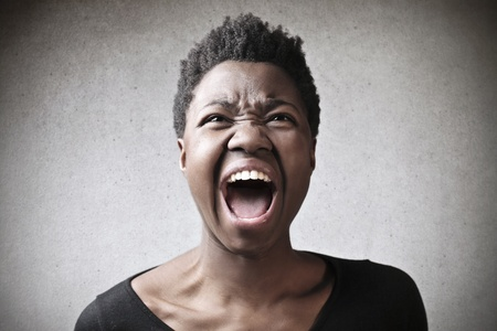 reprimand: portrait black woman screaming on gray background Stock Photo