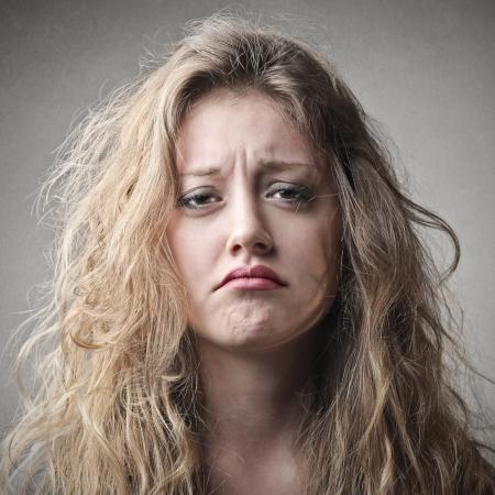 decepción: retrato de una mujer rubia triste en el fondo gris Foto de archivo