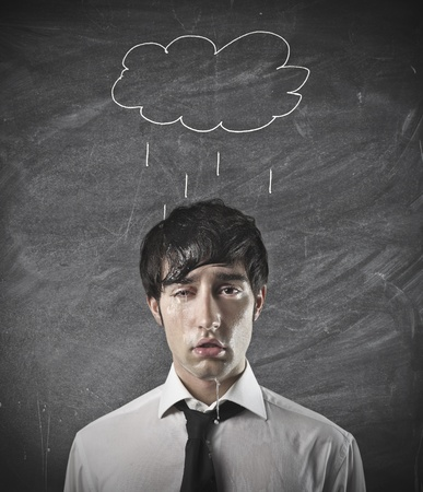 defeated: businessman wet with rain cloud over his head Stock Photo
