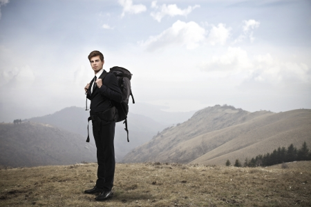 business man with backpack hiking in the mountains photo