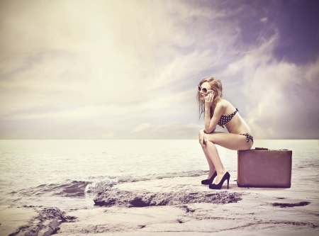 beautiful girl sitting on a suitcase in the desert photo