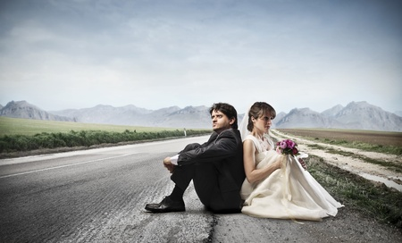 bride and groom sitting on a deserted road photo