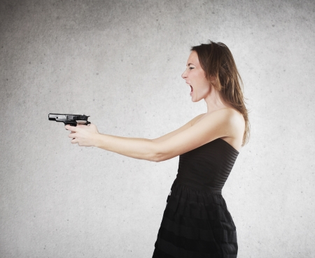 Profile angry woman with gun in hand on gray background photo