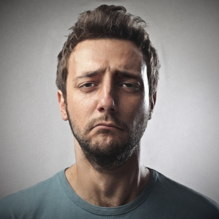 sorry: portrait of sad young man on gray background