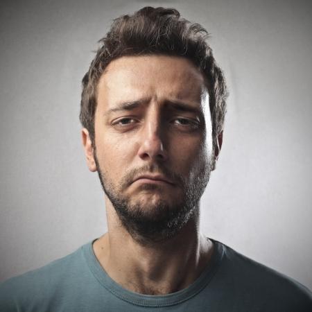 cara triste: Retrato de hombre joven triste en el fondo gris