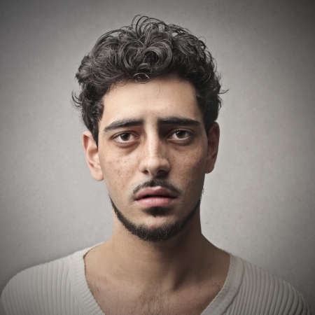 delusion: portrait of sad young man on gray background