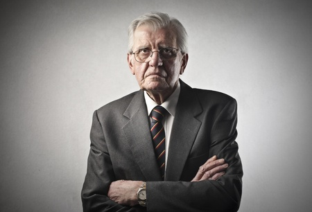 old business man: portrait of senior businessman with arms crossed on gray background Stock Photo