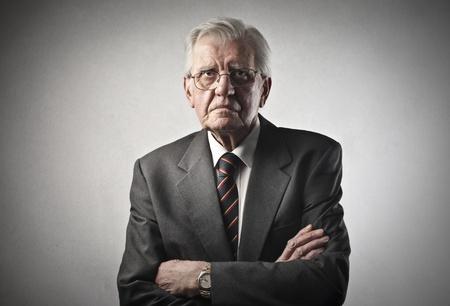 hombre preocupado: Retrato de hombre de negocios mayor con los brazos cruzados sobre fondo gris
