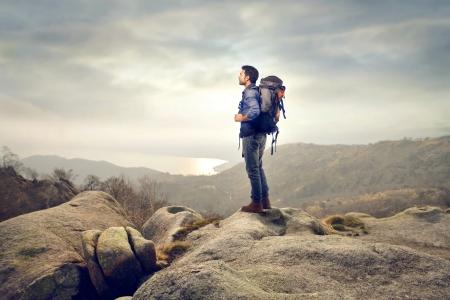 バックパック: 山中のバックパックと若い男