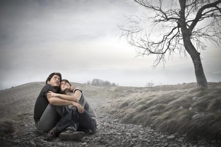 frightened couple sitting on the ground photo