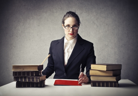 master: young teacher sitting at her desk with many books Stock Photo