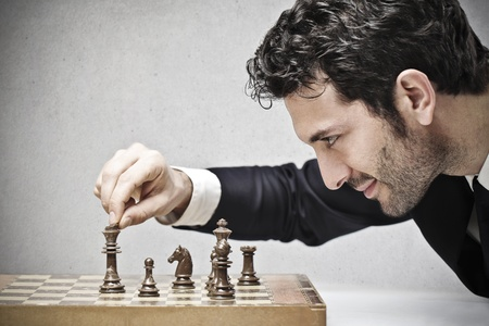 mind game: young businessman playing chess