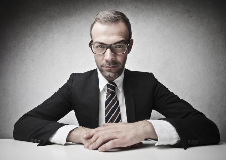serious businessman: serious businessman sitting at his desk Stock Photo