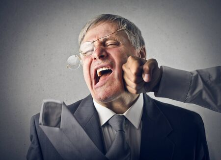 roughness: businessman senior receives strong punch in the face