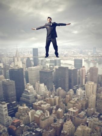 hombre asustado: equilibrio de joven empresario en la cuerda sobre la ciudad Foto de archivo