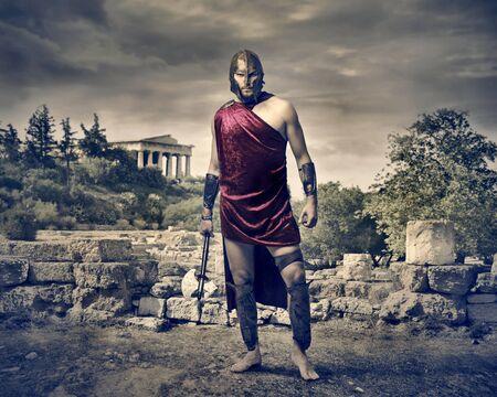 templo griego: guerrero con hacha en el paisaje con ruinas Foto de archivo