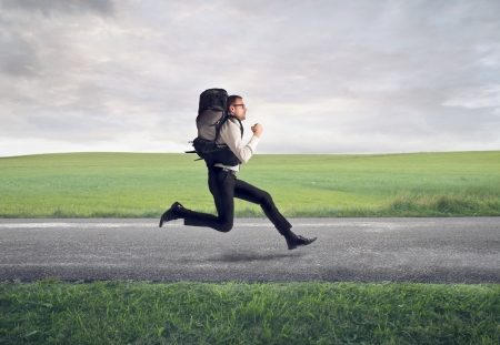 heavy: businessman running with backpack on the road