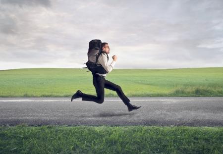 mochila: hombre de negocios que se ejecuta con la mochila en la carretera Foto de archivo