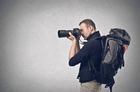 professionals: photographer takes a picture with professional camera