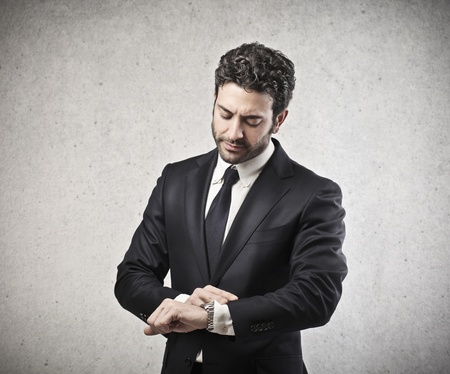 looking at watch: young businessman looking watch Stock Photo