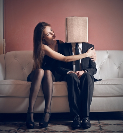 bashfulness: beautiful woman embraces man with head in box Stock Photo