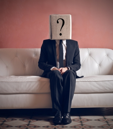 businessman sitting on the couch with his head in the box photo