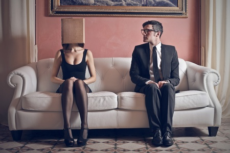 shy girl: man looks at beautiful woman with head in the box on the couch