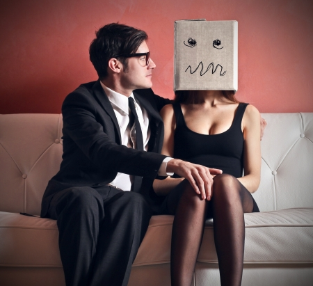 bashfulness: man embraces beautiful woman with head in the box on the couch Stock Photo