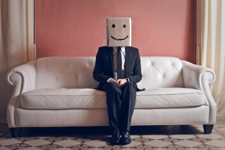 head home: happy businessman with head in the box on the couch