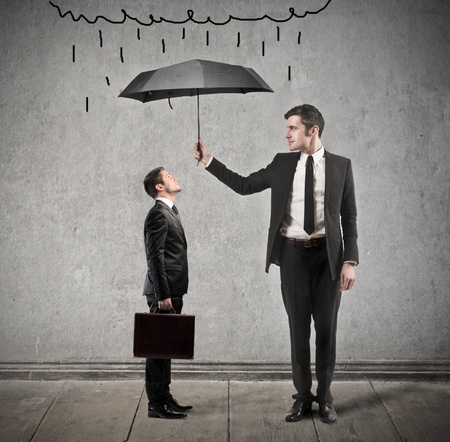 businessman with umbrella protects another man