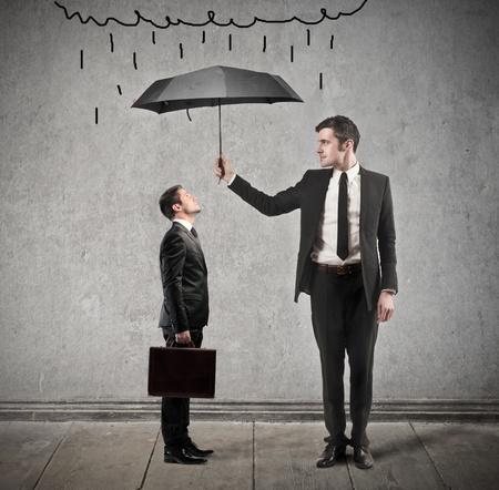 lluvia paraguas: hombre de negocios con paraguas protege a otro hombre