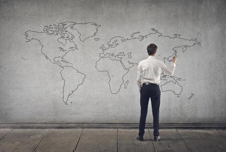 wall maps: hombre de negocios joven escribe en el mapa