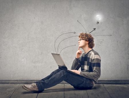 hombres jovenes: joven sentado en el suelo con el portátil Foto de archivo