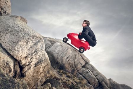 rock climb: young businessman climbs mountain with small red car
