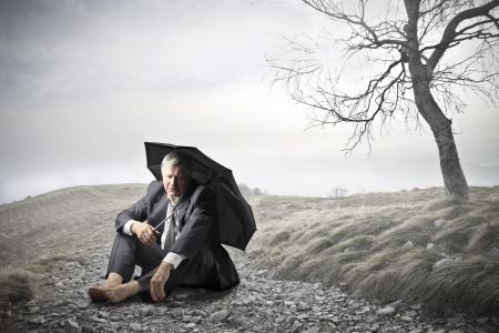 uomo sotto la pioggia: uomo d'affari seduto a terra con l'ombrello