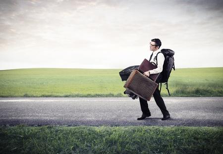 bagage: jeune homme d'affaires avec beaucoup de bagages sur la route Banque d'images